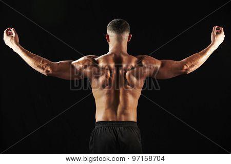 Male bodybuilder flexing muscles, back view