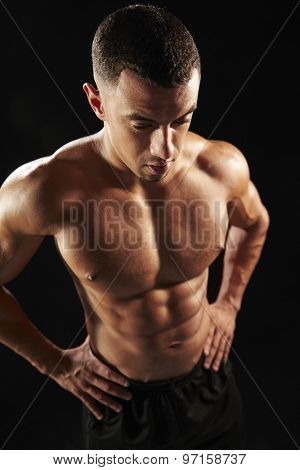 Male bodybuilder with hands on hips, elevated view