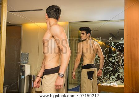 Young Man Admiring His Muscles in Mirror