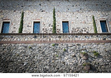 Stone Wall Of A Medieval Fortress With  Windows And A Small Hanging Garden.