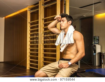 Muscular shirtless male athlete drying sweat with towel