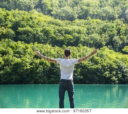 Young man, arms spread open enjoying freedom in front of lake