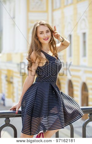 Close up Portrait, Young beautiful blonde woman in black dress posing outdoors in sunny weather