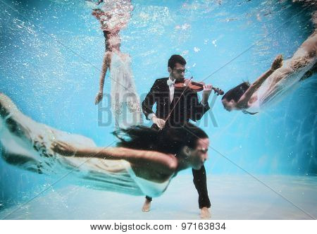 Violinist playing underwater with muse swimming around