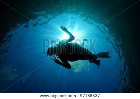 Scuba diver silhouette and sun