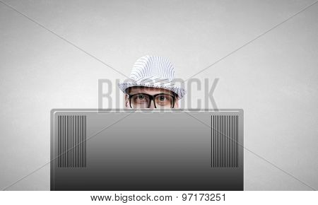 Young man looking out above laptop monitor