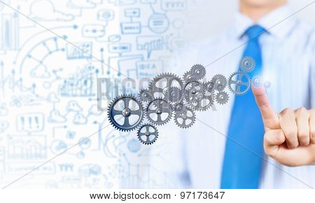 Close up of businessman touching gears mechanism with finger