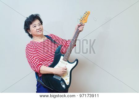 Portrait Of Adult Asian Woman With Electric Guitar Specialty Toned, Studio Shot