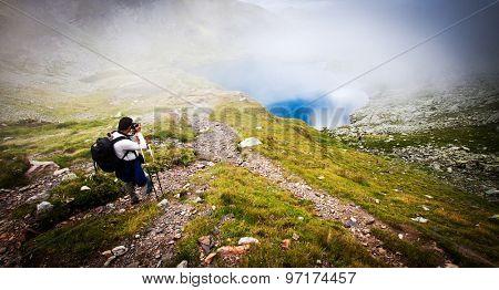 Hiker taking photos at Capra lake in Fagaras mountains, Romania