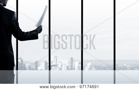 Businessman standing against office window reading documents