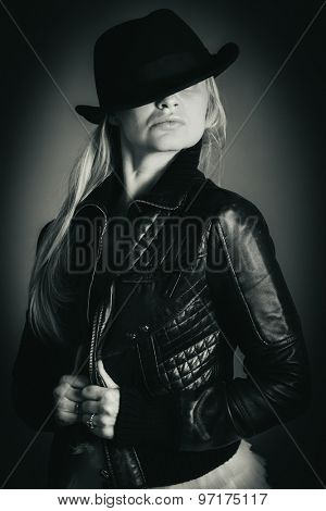 Black and white portrait of a girl in a hat and leather jacket