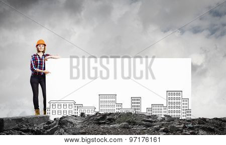 Young woman builder wearing helmet and holding banner with construction sketches