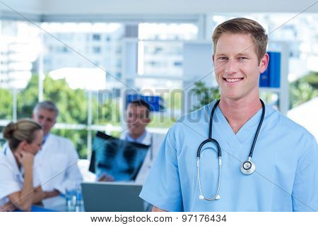 Handsome smiling doctor looking at camera in medical office