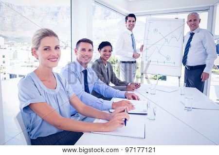 Business team during meeting smiling at camera in the office