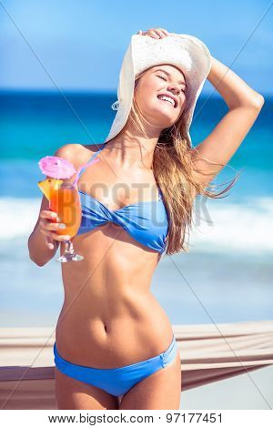 Pretty woman holding cocktail at the beach