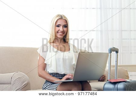 Woman with suitcase and laptop after traveling at home