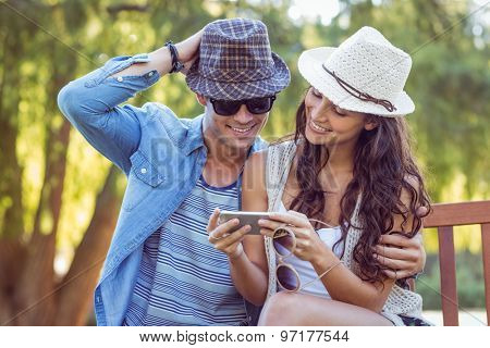 Cute couple looking looking at their selfies on a sunny day