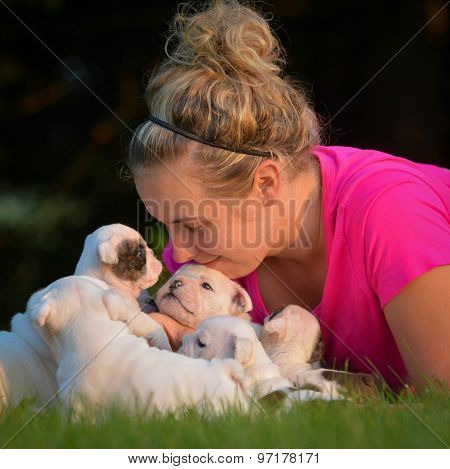 woman playing in the grass with litter of puppies