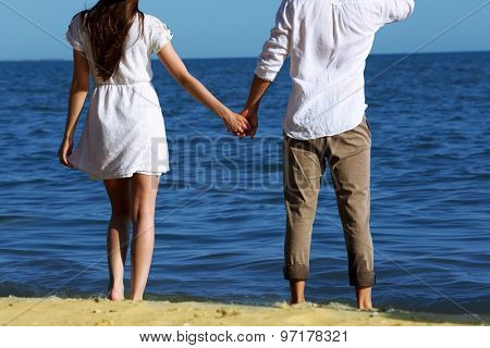 Young couple holding hands on beach