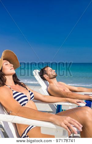 Happy couple relaxing on deck chair at the beach on a sunny day