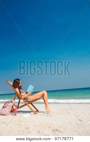 Pretty brunette reading a book on deck chair at the beach