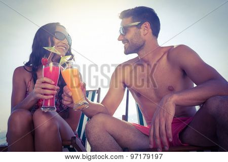 happy couple smiling and drinking cocktail at the beach