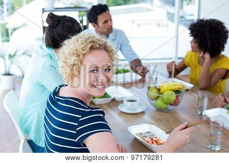 Young businesswoman having lunch with her colleagues