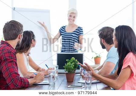 Casual young businesswoman giving a presentation to her colleagues