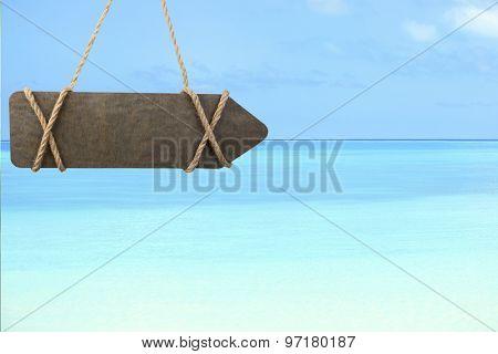 Wooden sign arrow on ocean background