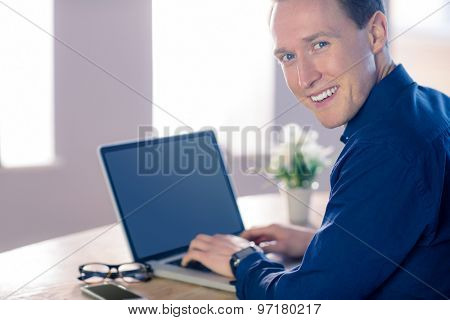 Happy businessman with his laptop smiling at camera in his office