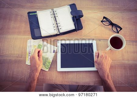 Money bundle and digital tablet on a wood table