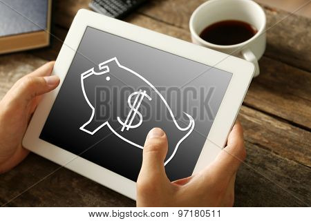 Money concept. Hands holding digital tablet with piggy bank image on it, close-up