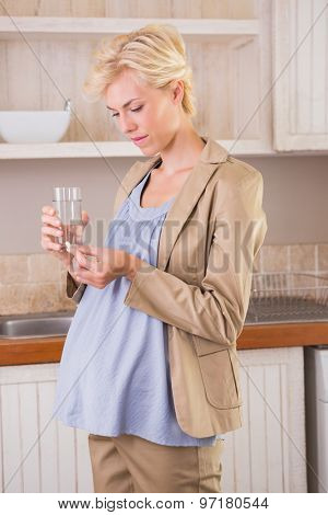 Blonde pregnancy taking a vitamin in the kitchen