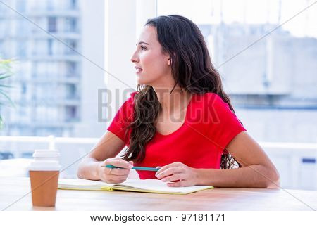 Concentrated woman taking notes during a meeting at office