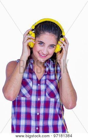 Pretty brunette listening music with headphone and looking at camera on white background