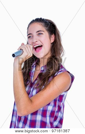 Happy pretty brunette singing on microphone on white background