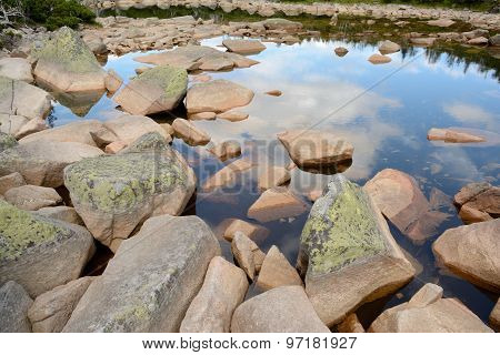 Stones In Lake In Mountains.