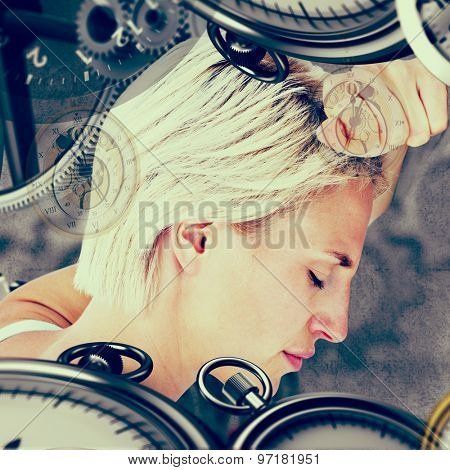 Sad blonde woman with her head on wall against grey background