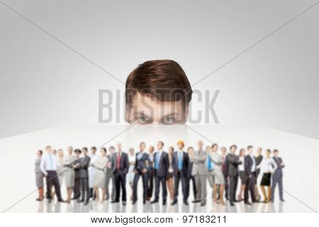 Young man looking from under table on large group of business people
