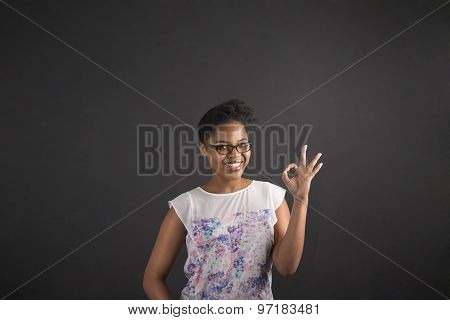African Woman With Perfect Hand Signal On Blackboard Background