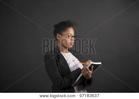 African Woman Writing In Book Diary On Blackboard Background
