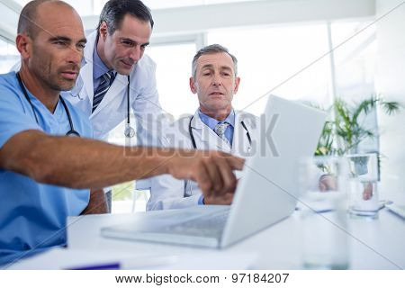 Doctor showing laptop pc to his colleagues in medical office