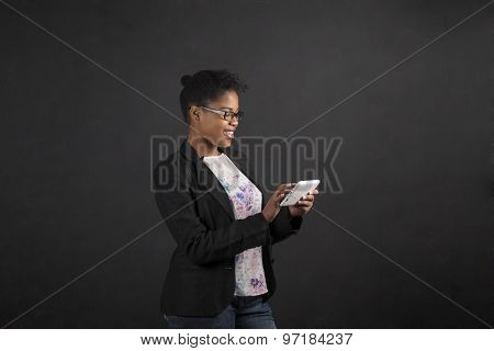 African Woman With Tablet On Blackboard Background