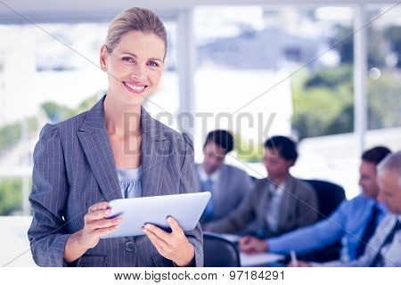 Businesswoman holding tablet and looking at camera in the office