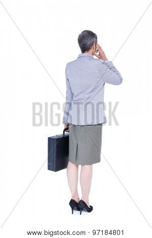 Wear view of businesswoman stranding with suitcase on white background