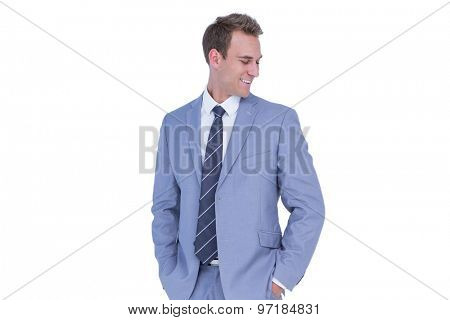 Happy handsome businessman smiling with hands on pockets on white background