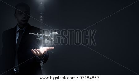 Close up of businessman hands holding airplane sign