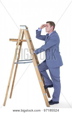 Businessman standing on ladder looking on white background