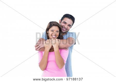 Happy couple embracing and looking at the camera on white background