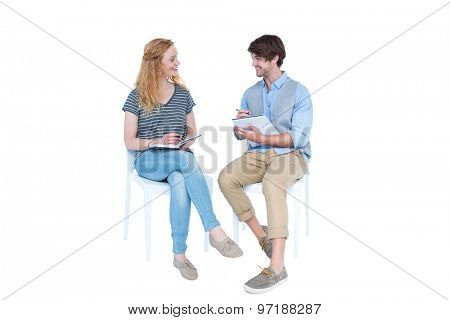 Happy couple speaking and taking notes on white background